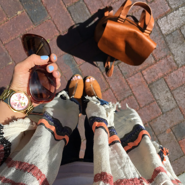 Striped Poncho, tassel backpack, prada sunglasses