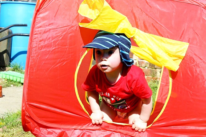 A small 1 year old boy wearing a red top and blue sunhat is peeking out of a red tent.