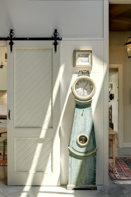 Sliding vintage barn door and Swedish mora clock - found on Hello Lovely Studio