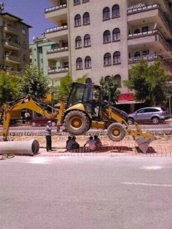 workmen having lunch under digger safety fail