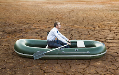 a businessman is in a boat stranded in the desert