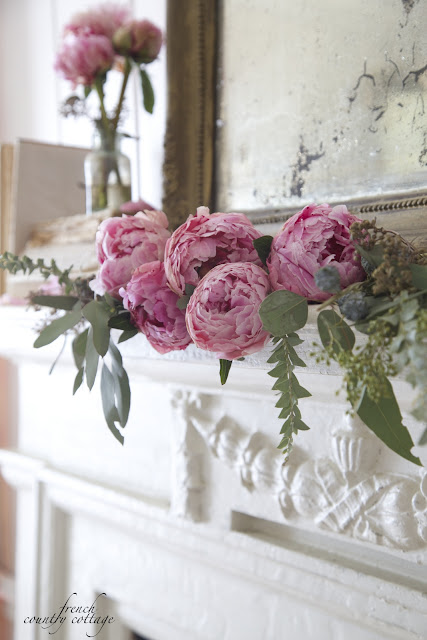 Pink peonies and eucalyptus on mantel