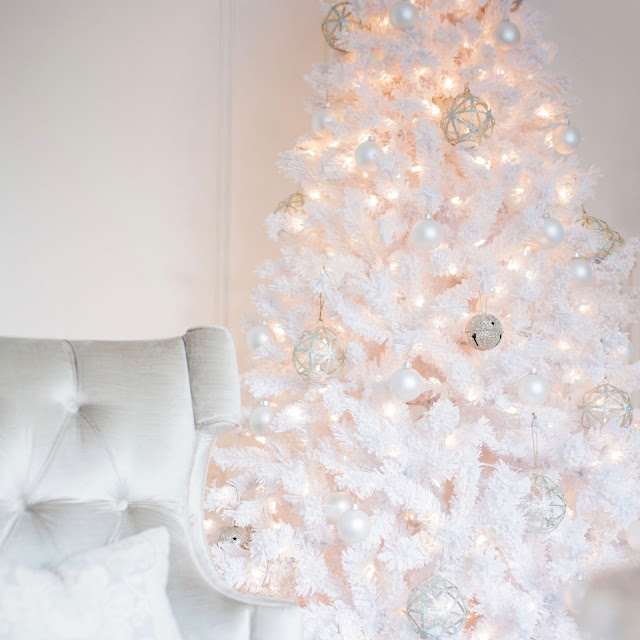 Silver Grey Velvet chair beside fluffy white flocked Christmas tree with glitter jingle balls and pottery barn ornaments