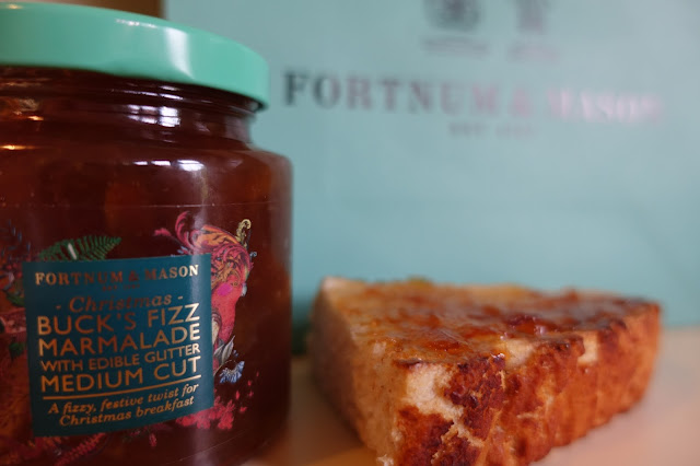 A jar of Marmalade with Edible Glitter in front of a Fortnum & Mason bag and next to a slice of toast with marmalade on