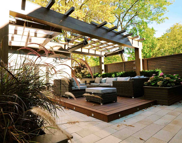alt=deck podium clad in tropical hardwood | outdoor furniture arranged around a fire table | suspended has heaters | ornamental grass in foreground planter
