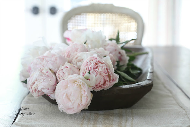 dough bowl filled with peonies on grainsack on table