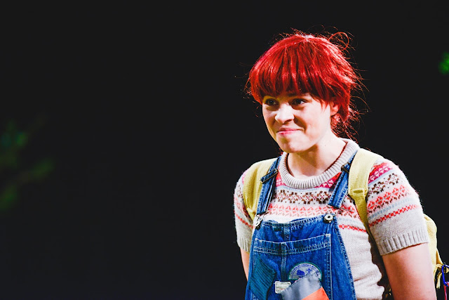 a girl with red hair in dungarees smiling.