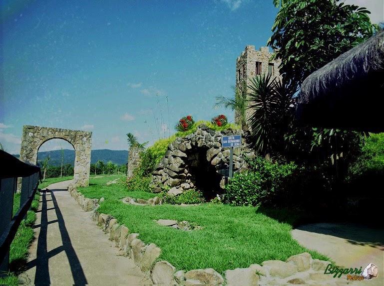 Caminho no jardim com o piso de cimentado desempenado com a gruta de pedra, o pórtico de pedra e a torre de pedra.
