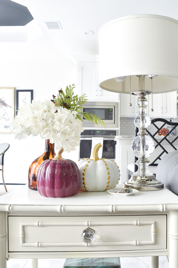 A white bamboo end table with fall decor, hydrangeas and pumpkins in an eclectic living room