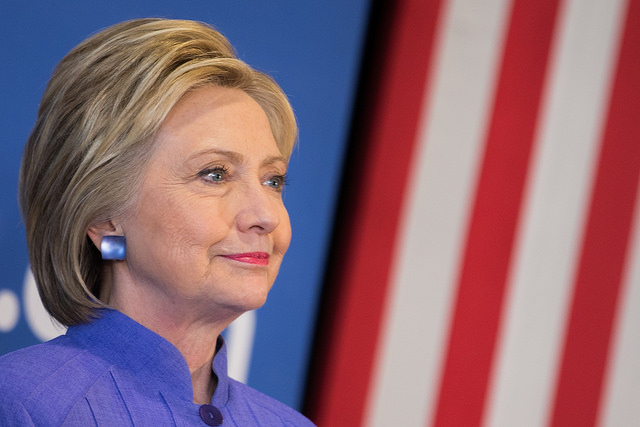 image of Hillary Clinton in profile, smiling slightly, with a US flag in the background