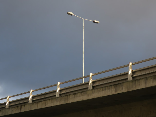 Double lampost on concrete bridge carrying main road with blank blue sky.