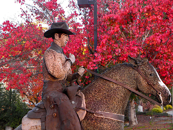 Cowboy and horse sculpture with flaming red trees