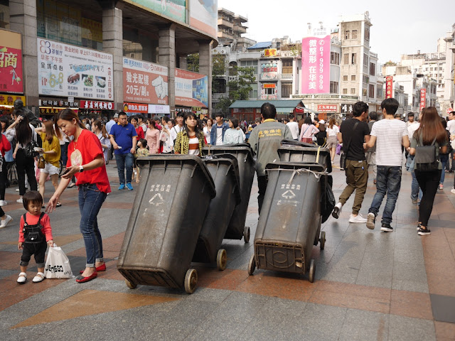 sanitation working pulling five trash bins
