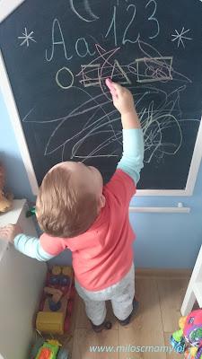 mały chłopiec maluje kredą
