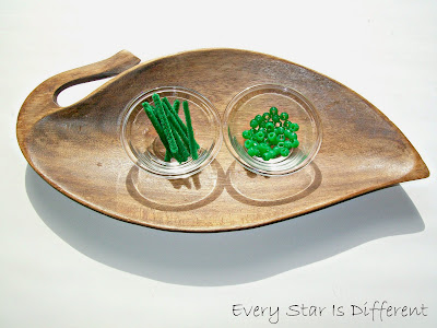 Stringing two green beads to represent the Montessori bead bar.