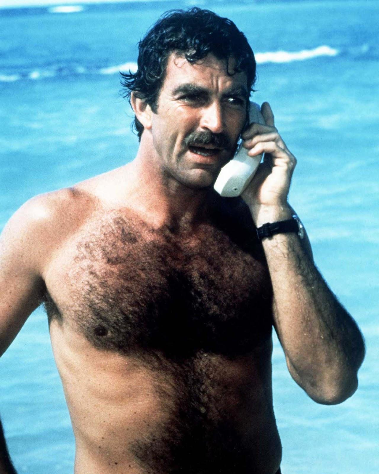 """Tom Selleck, que interpreta o investigador particular Thomas Magnum, faz um telefonema da praia na série de TV """"Magnum PI"""". 1985."""