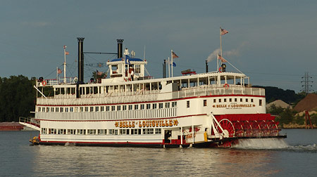 belle of louisville steam boart cruising on the river with the baddlewheel in the back and people on the deck