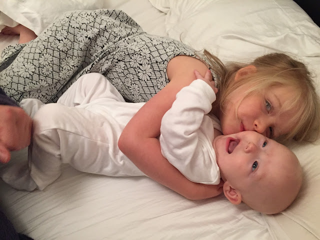 A big sister and her baby sister cuddling on a bed
