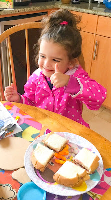 Little girl in a pink polka dot coat sits at a table eating a sandwich