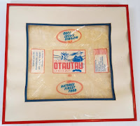 A framed cheese wrapper with graphics and labels Otautau Co-op Dairy Factory