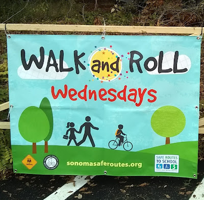 Banner, attached to metal gate frame, reads, 'Walk and Roll Wednesdays, sonomasaferoutes.org.' Image depicts human figures, an adult-sized walking holding the hands of a figure with skirt and pony-tail who is holding a lunch box. In front of them, a third figure rides a bicycle and wears a backpack. The trio of figures are depicted in a landscape of trees and green hills, against a blue-sky backdrop