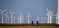 Workers walk near wind turbines for generating electricity, at a wind farm in Guazhou, China. (Credit: Carlos Barria / Reuters) Click to Enlarge.