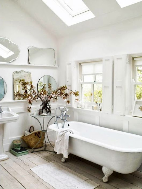 shabby chic bathroom with antique mirrors and claw foot bathtub