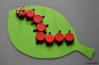 gąsienica z plastikowych nakrętek na liściu