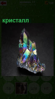 на столе стоит цветной кристалл, который переливается разными цветами