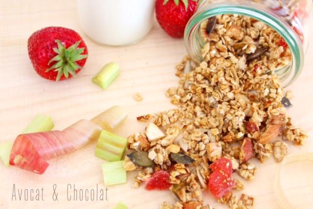"""alt=""""granola fraise-rhubarbe qui déborde d'un pot en verre sur une planche en bois"""""""