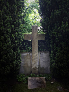 photographs of a cross in a cemetery on a rainy day by andreas warren matti