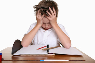 Image of child struggling to focus in a classroom.