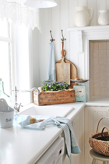 Swedish farmhouse kitchen with wood cutting boards and country decor - found on Hello Lovely Studio