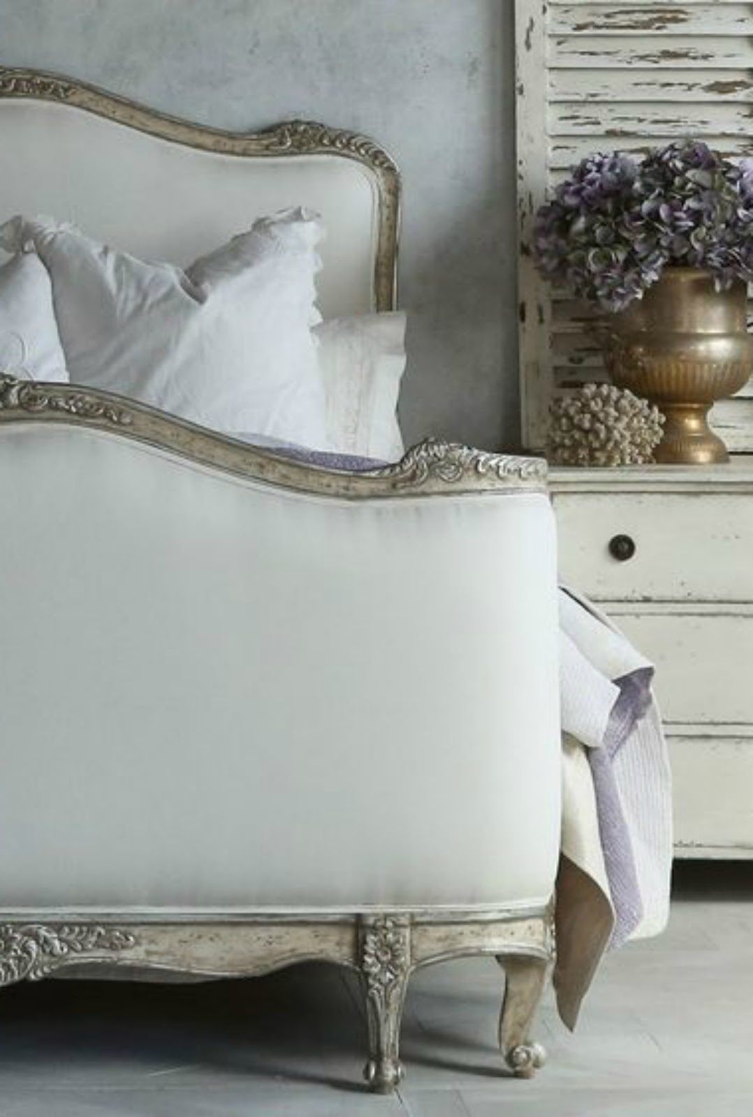 Elegant French farmhouse bedroom with magnificent bed and weathered shutter on Hello Lovely Studio