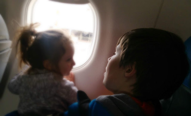 A little girl sitting on an older boy's lap looking out of an aeroplane window.