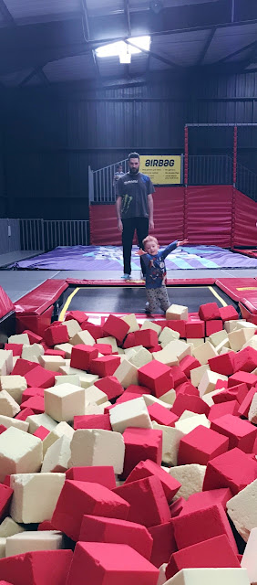 Little boy bouncing from a trampoline into a foam pit as he Daddy watches in the background