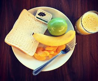 Teller mit Toast, Mandarinen, grünem Apfel auf braunem Tisch, Orangensaft