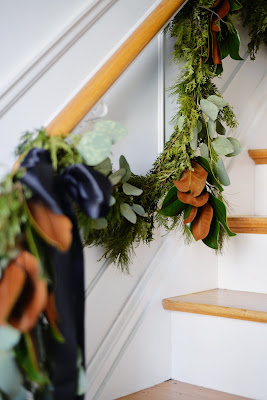 christmas garland swag on staircase with pine cedar magnolia silver dollar eucalyptus and black satin ribbon