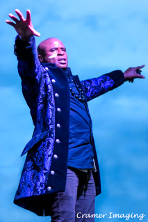 Cramer Imaging's professional quality concert photograph of singer Alex Boyé in costume standing against the sky in Firth, Idaho