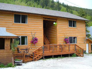 Log sided condos, autum gold, with 2 large hanging baskets of pink flowing flowers.