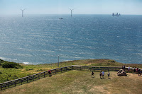The project's wind turbines, about three miles away, can be seen from shore on Block Island, but island residents have been largely supportive. (Credit: Kayana Szymczak / The New York Times) Click to Enlarge.
