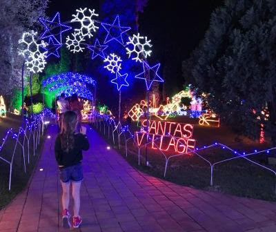 "Girl walking through the Garden of Lights: ""Santas Village"""