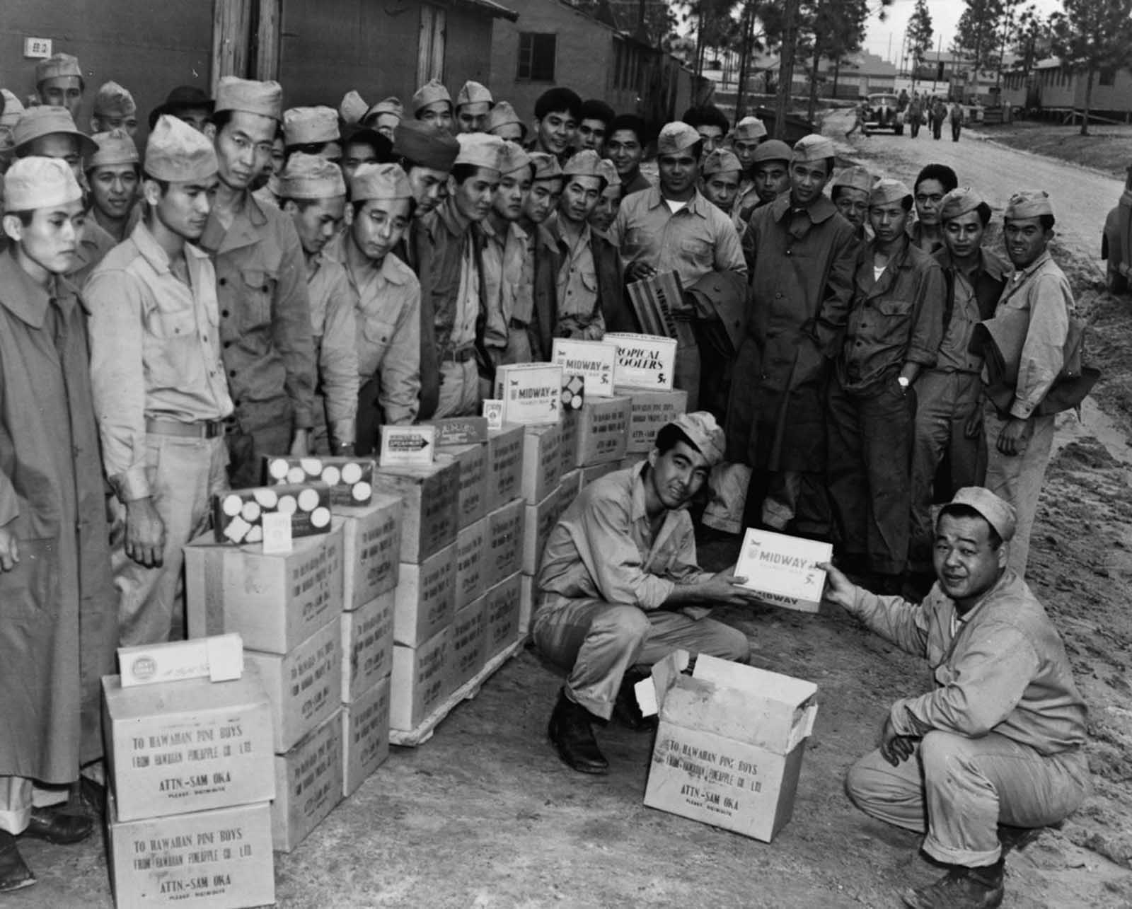Soldiers distribute candies and cigarettes donated by a Hawaiian pineapple company. 1943.