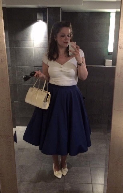 Mirror selfie of 1950s style retro woman in fifties pin up style rockabilly dress with vintage style hair
