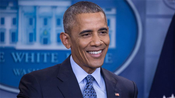 image of President Obama in the White House press room, smiling, during his final press conference