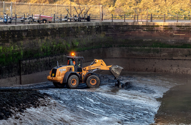Photo of a digger clearing mud from the bottom of the marina slipway