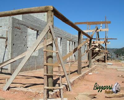 Detalhe dos pilares de madeira com os frechais de madeira roliça em cima das muretas de pedra na execução da construção rústica com alvenaria de bloco.