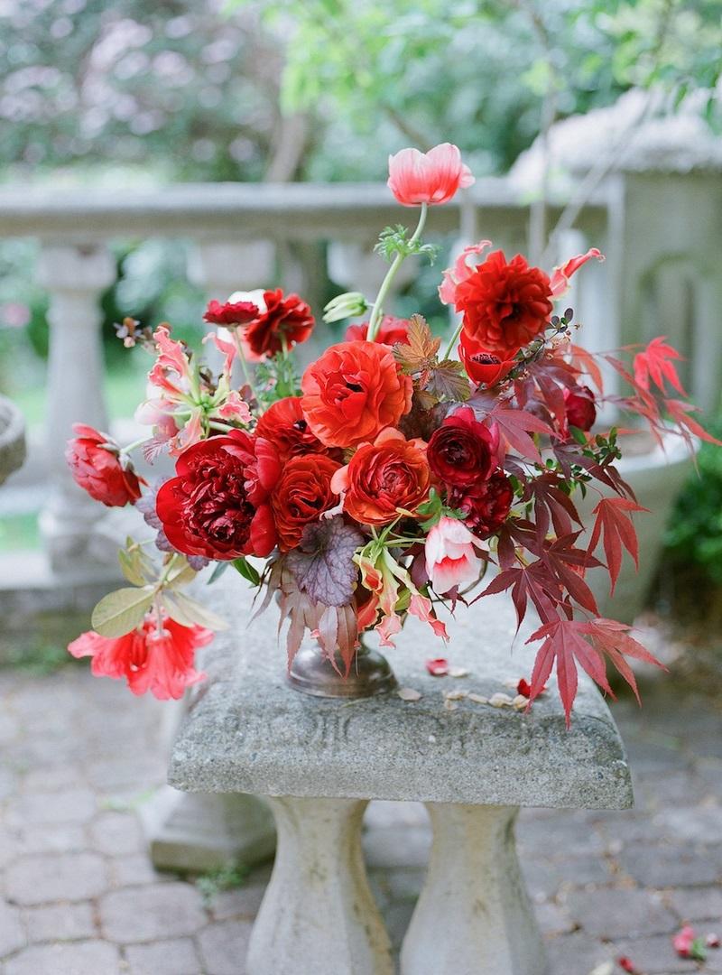 banco de piedra y jarrón con flores rojas