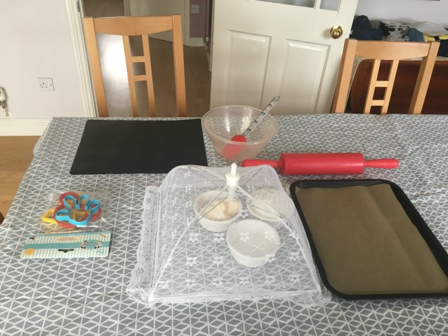 played-out-on-table-bowl-disney-spatula-mickey-mouse-cutters-flour-sugar-spread-under-a-cover-rolling-pin-and-baking-tray