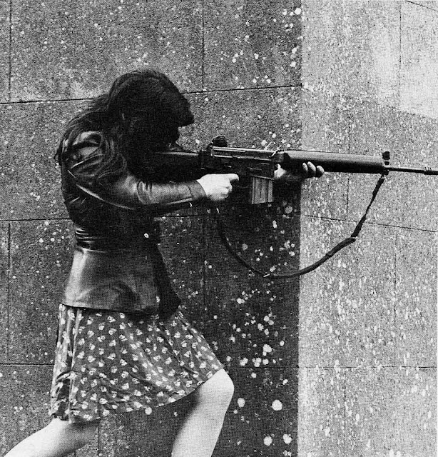 A woman IRA volunteer on active service in West Belfast with an AR18 assault rifle.